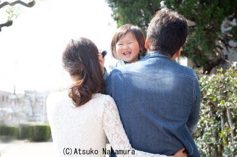 子どもを抱っこするパパと微笑むママ