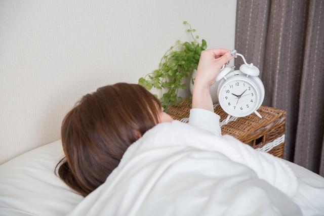 寝起きで目覚まし時計を止める女性
