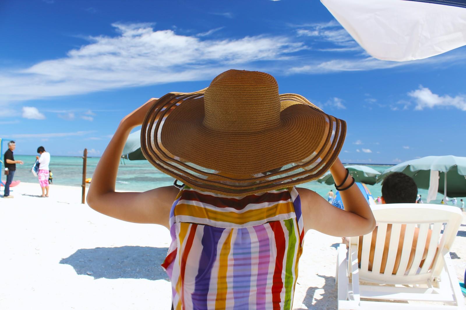 ビーチで大きな帽子をかぶる女性