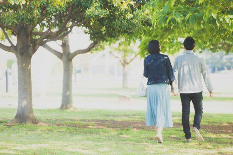 手をつないで公園を歩く夫婦