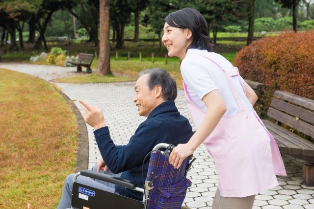 車椅子を押す介護職員