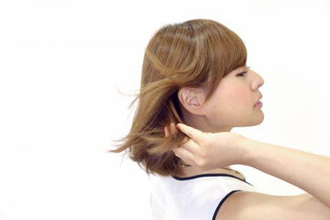 風に髪をなびかせている女性