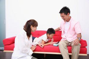 鍵盤ハーモニカの練習をする子供と両親
