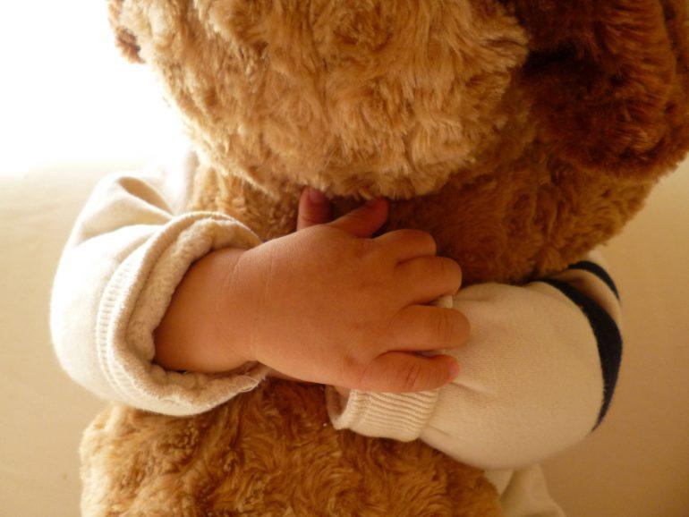 テディベアを抱きしめる子ども