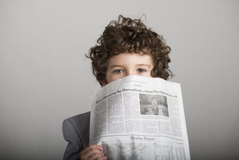 新聞で顔を隠す女の子