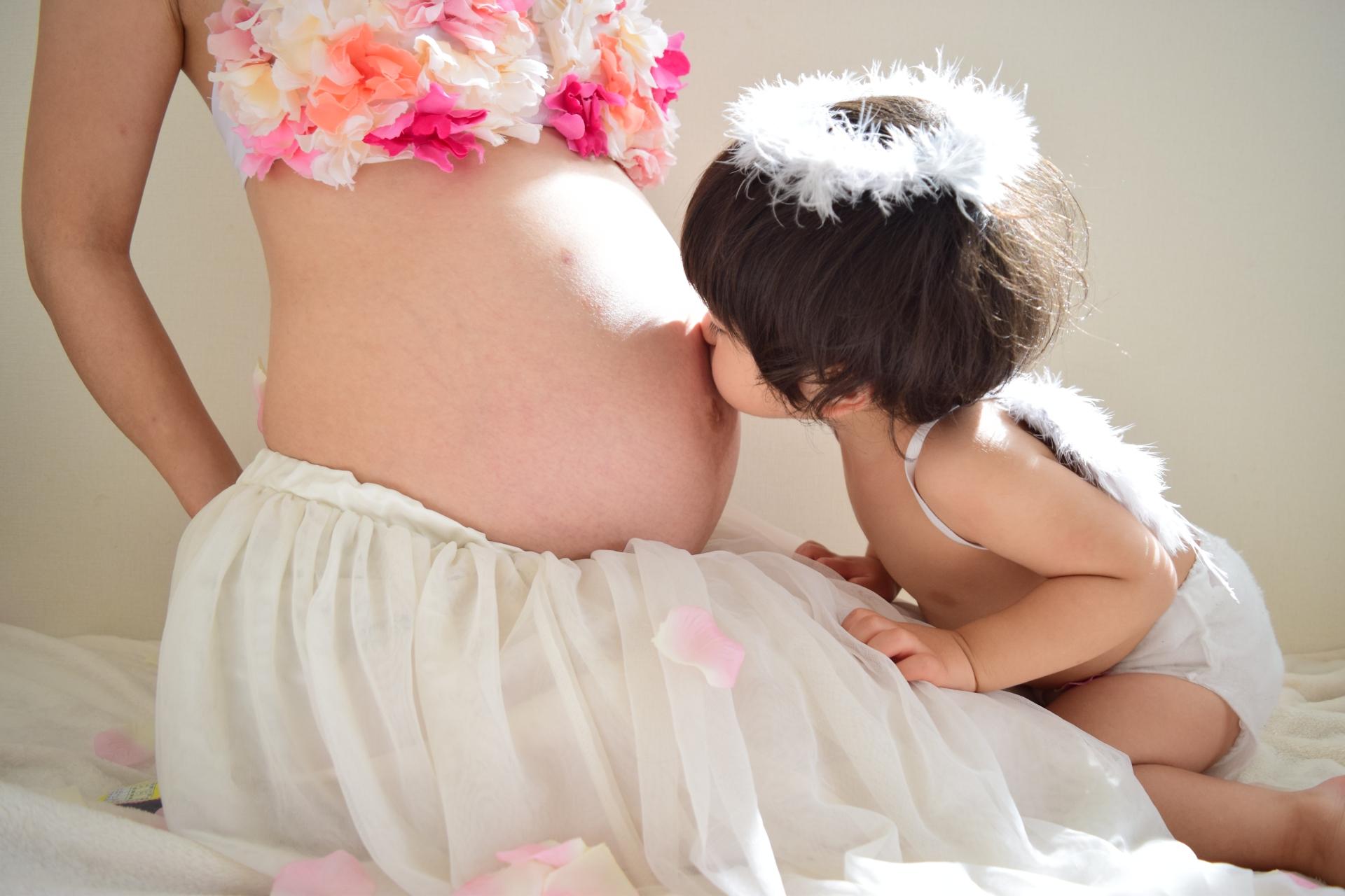 お腹の大きなママにキスする子ども
