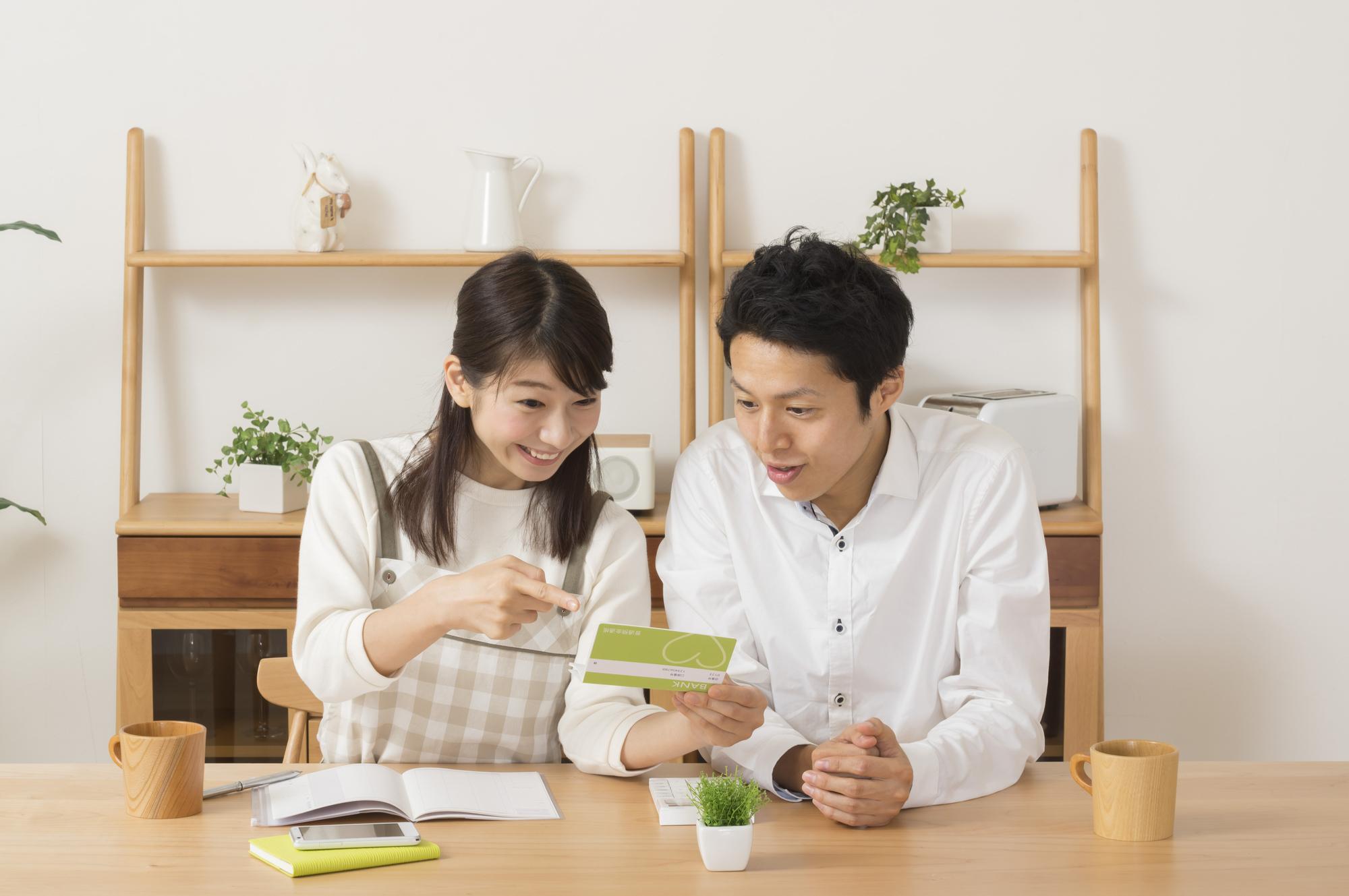 預金通帳を眺める夫婦