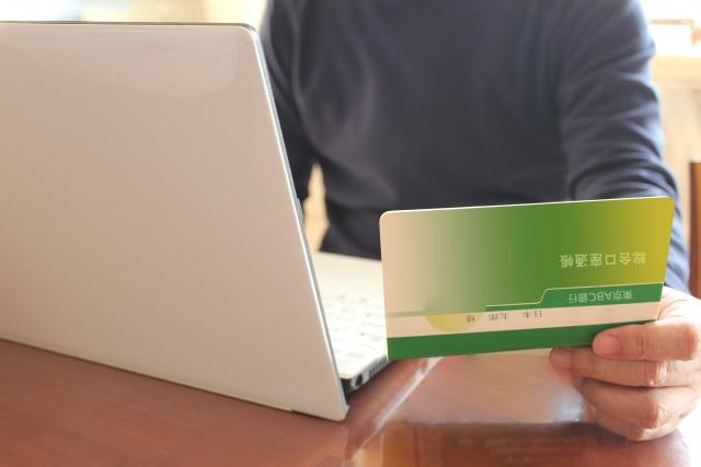 通帳を見ながらパソコンを操作